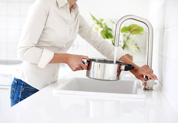 Femme qui remplit une casserole avec de l'eau osmosée pour cuisiner
